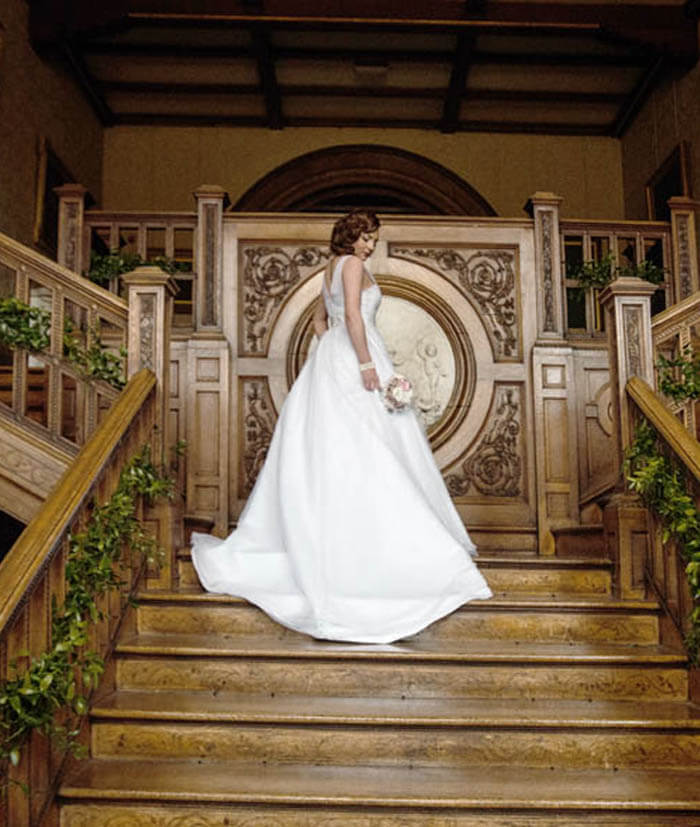 Beautiful bride posing on detailed wooden stairway