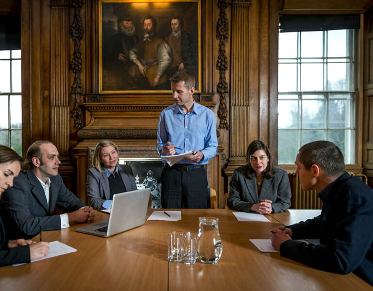 Man and guests seated in meeting in the Edwin Muir room, available for meetings and conference venue hire