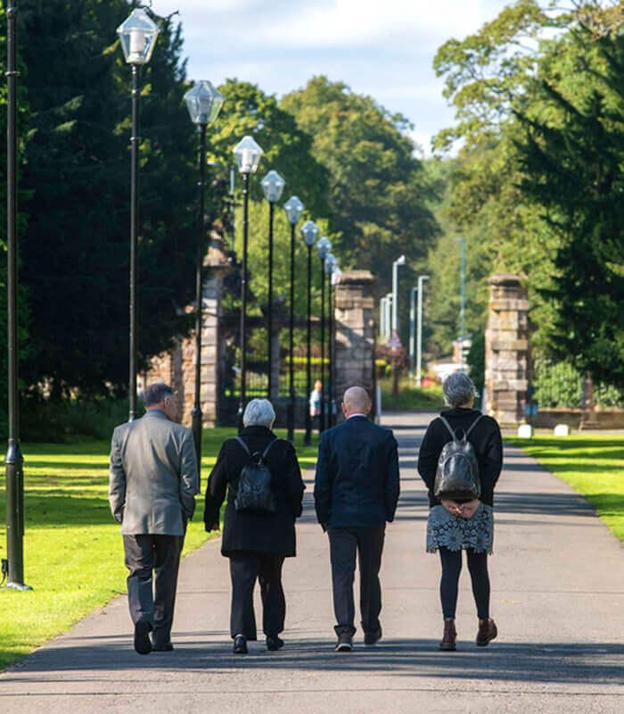 Image of people walking along the Newbattle Abbey path.