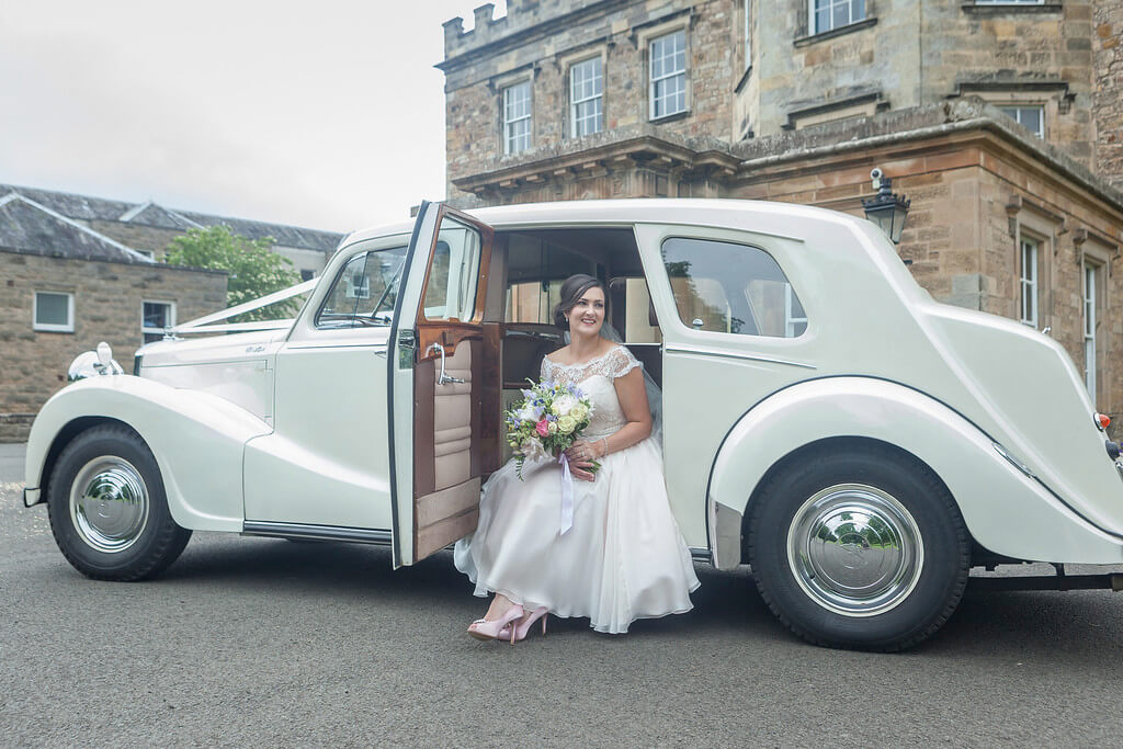 Beautiful Bride posing in Vintage car outside Newbattle Abbey Wedding Venue Scotland - © Mike Cook Photography