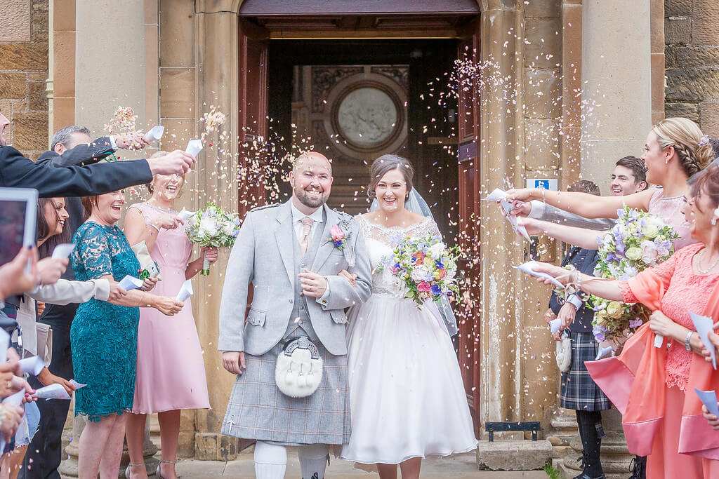 Bride and Groom with guest throwing confetti at Newbattle Abbey Wedding Venue Scotla