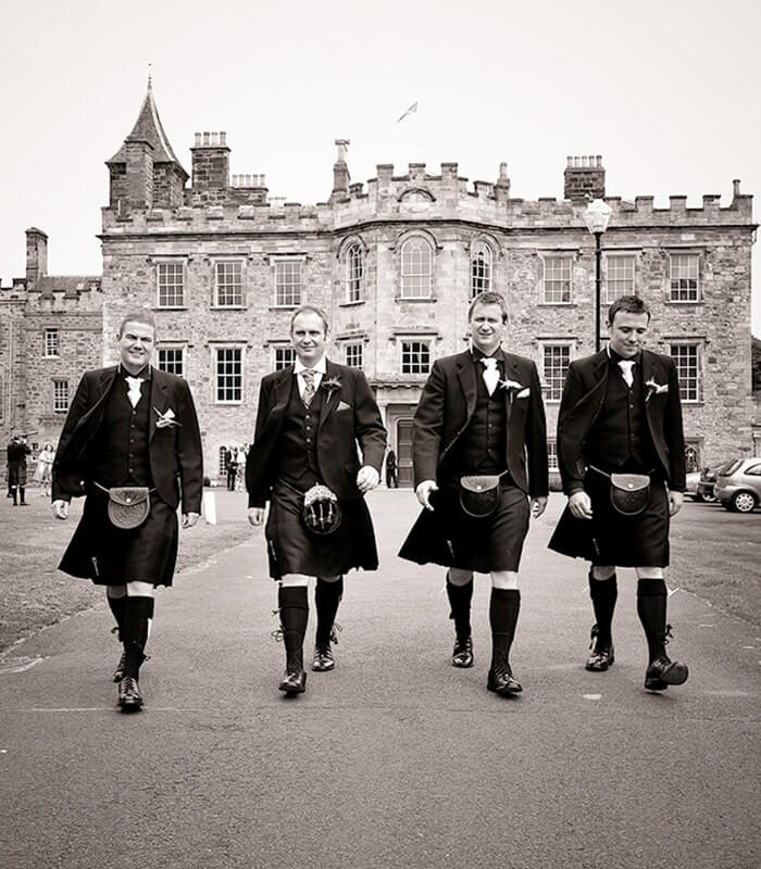 4 Groomsmen walking away from Newbattle Abbey wedding Venue