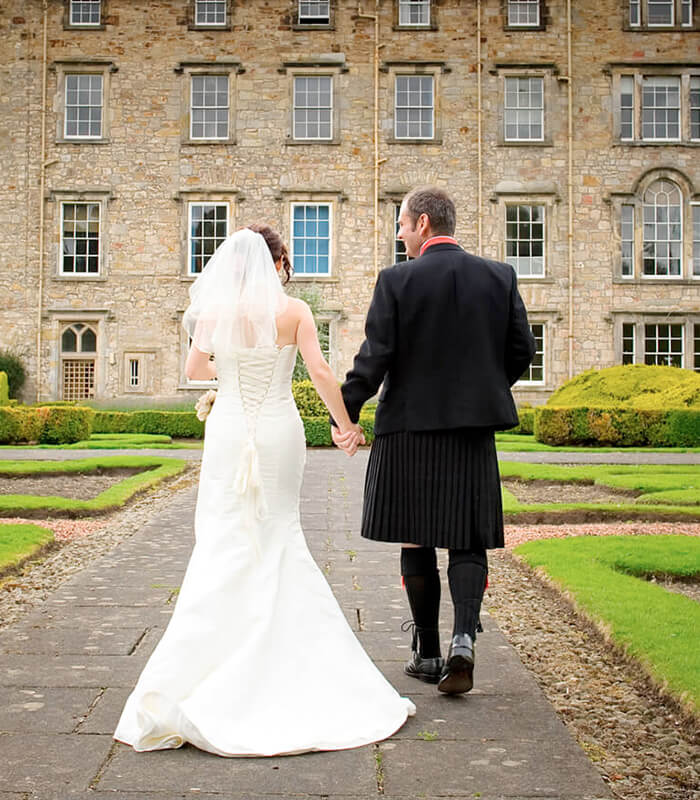 Bride and Groom walking hand in hand towards Newbattle Abbey wedding Venue